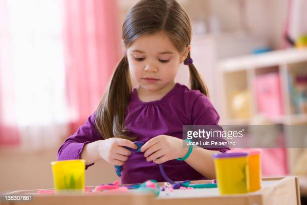 mixed race girl playing with clay - clay stock pictures, royalty-free photos & images