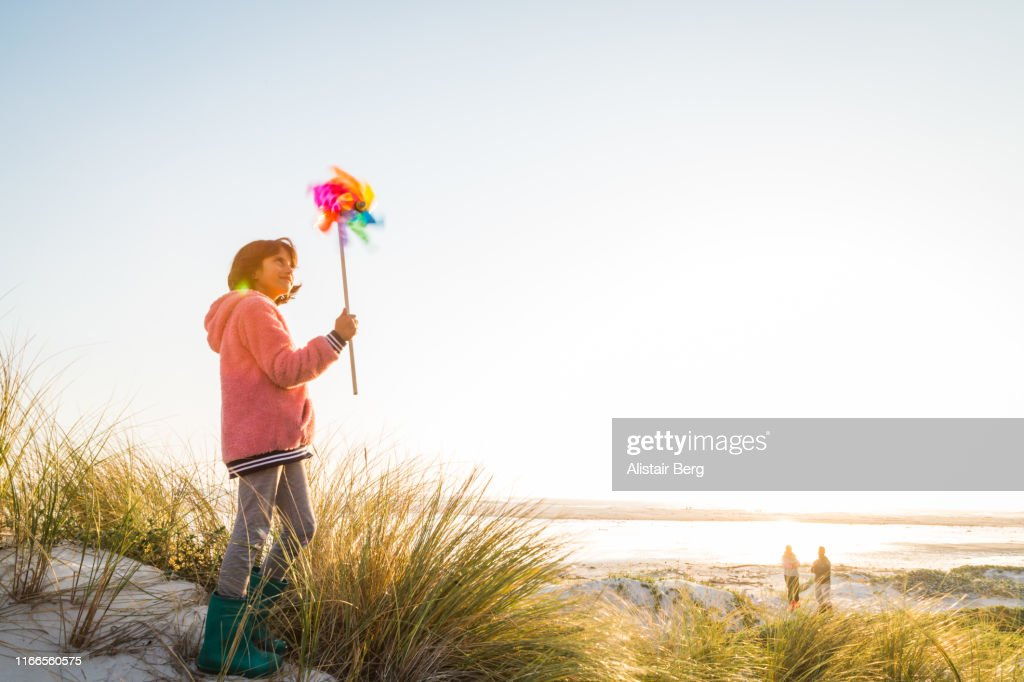 Mixed race girl playing with pin wheel toy at the beach : ストックフォト