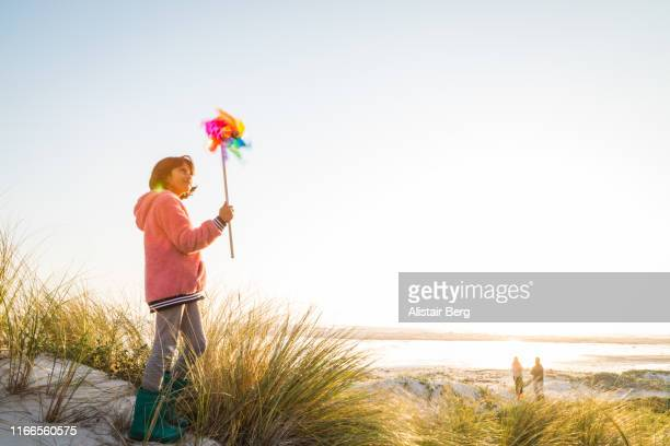 mixed race girl playing with pin wheel toy at the beach - 風車塔 ストックフォトと画像