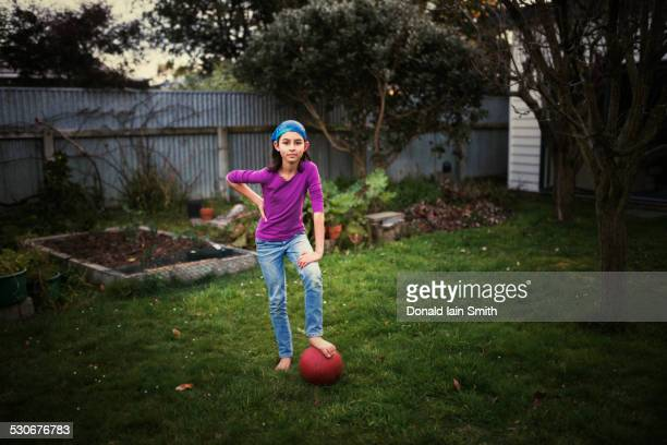 Mixed race girl playing with soccer ball in backyard