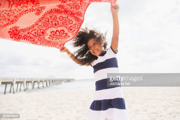 Mixed race girl playing with towel on beach