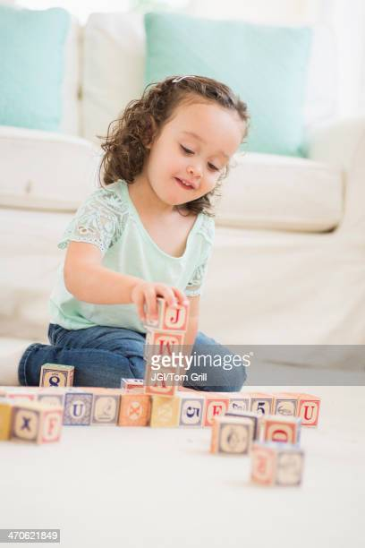 Mixed race girl playing with wooden blocks