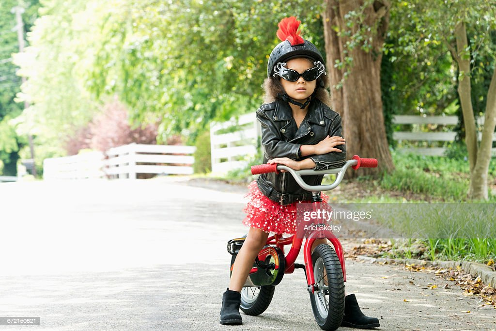 Mixed Race girl posing with attitude in leather jacket on bicycle : Stock Photo