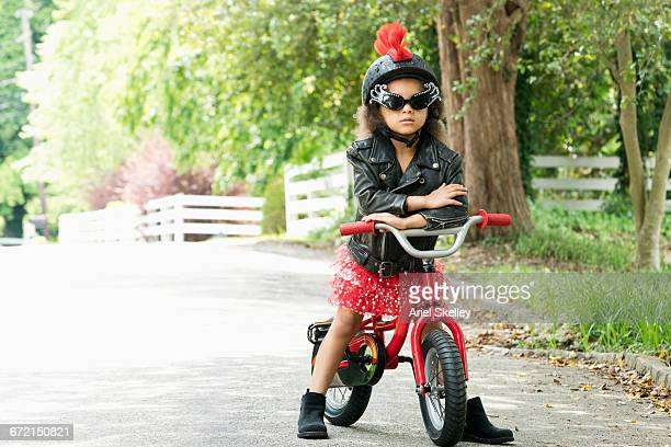 mixed race girl posing with attitude in leather jacket on bicycle - rébellion photos et images de collection