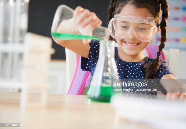 Mixed race girl pouring liquid in chemistry class