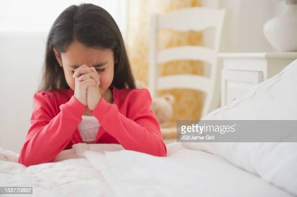 Mixed race girl praying in bedroom