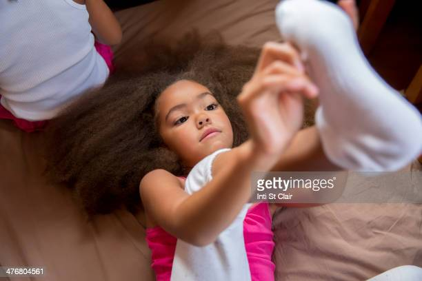 mixed race girl pulling on sock - adjust socks stock pictures, royalty-free photos & images