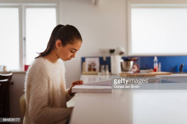 Mixed race girl reading book in kitchen