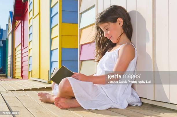 mixed race girl reading book near colorful beach hut - cabine de plage photos et images de collection