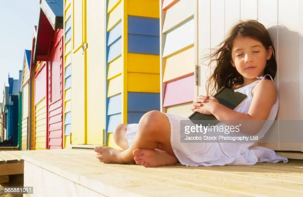 Mixed race girl reading book near colorful beach hut