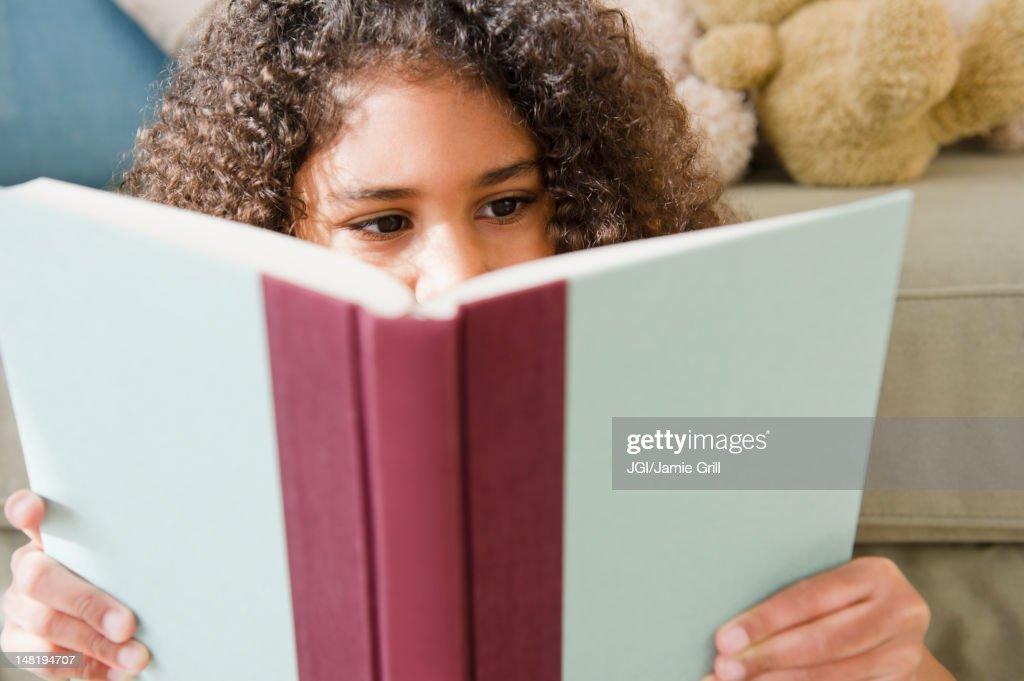 Mixed race girl reading book : Foto de stock