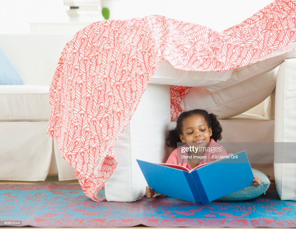Mixed race girl reading in living room fort : Stock Photo