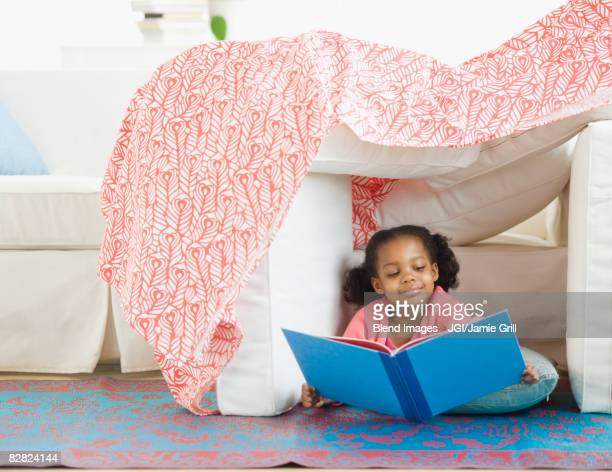 mixed race girl reading in living room fort - fortress stock pictures, royalty-free photos & images