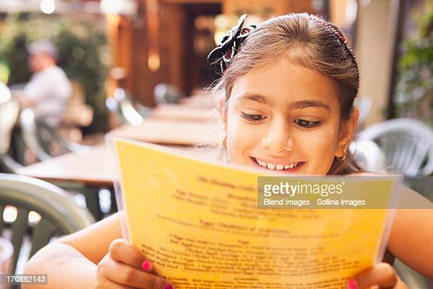 Mixed race girl reading menu in restaurant