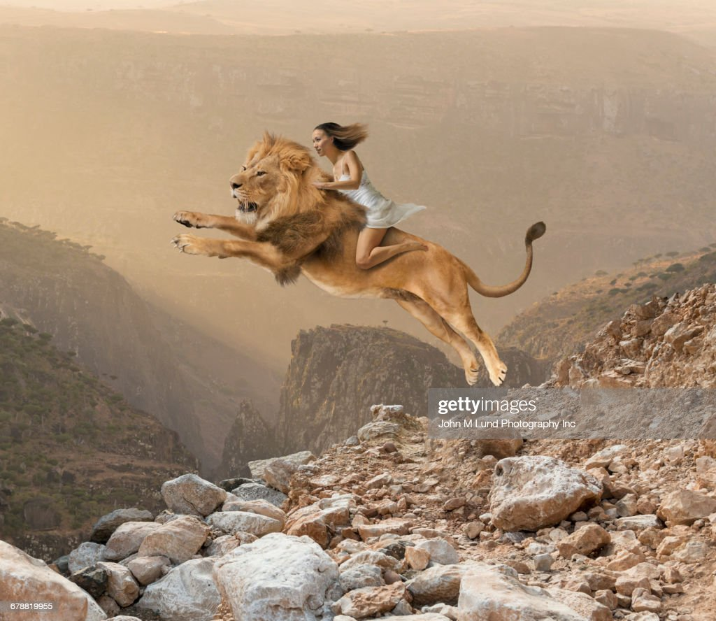 Mixed Race girl riding lion jumping on mountain : Stock Photo