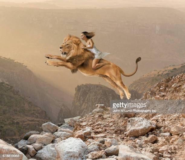 Mixed Race girl riding lion jumping on mountain