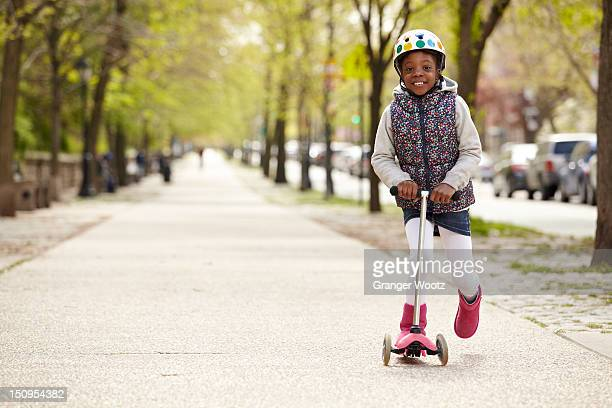 Mixed race girl riding on push scooter on sidewalk
