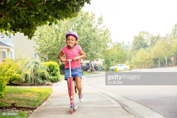 Mixed race girl riding scooter on sidewalk