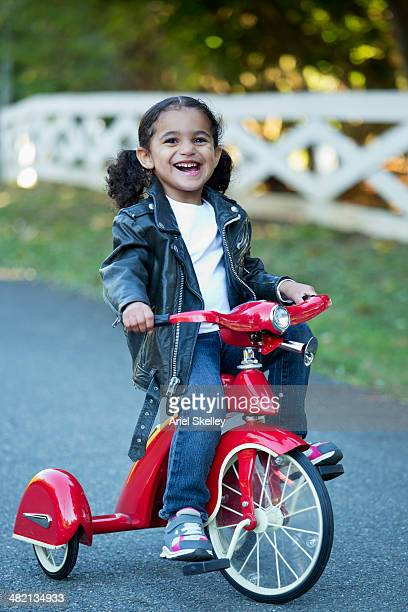Mixed race girl riding tricycle
