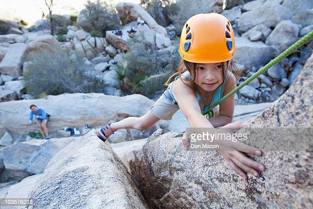 Mixed race girl rock climbing