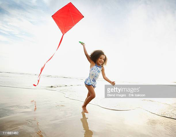 Mixed race girl running with kite on beach