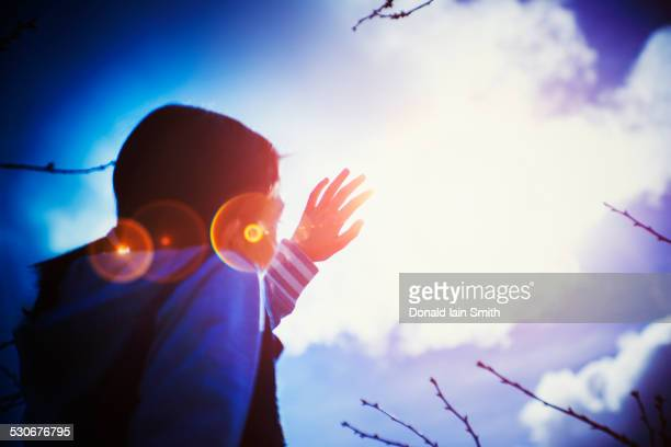 mixed race girl shielding herself from sun lens flare - hot indian girls stock photos and pictures
