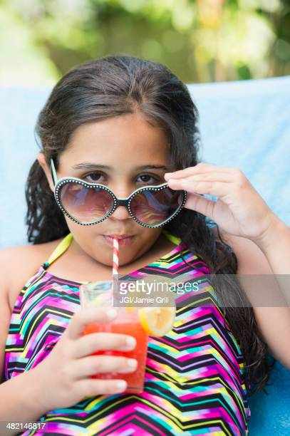 mixed race girl sipping juice at poolside - diva human role stock photos and pictures
