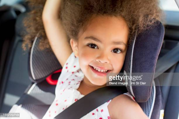 Mixed race girl sitting in car seat