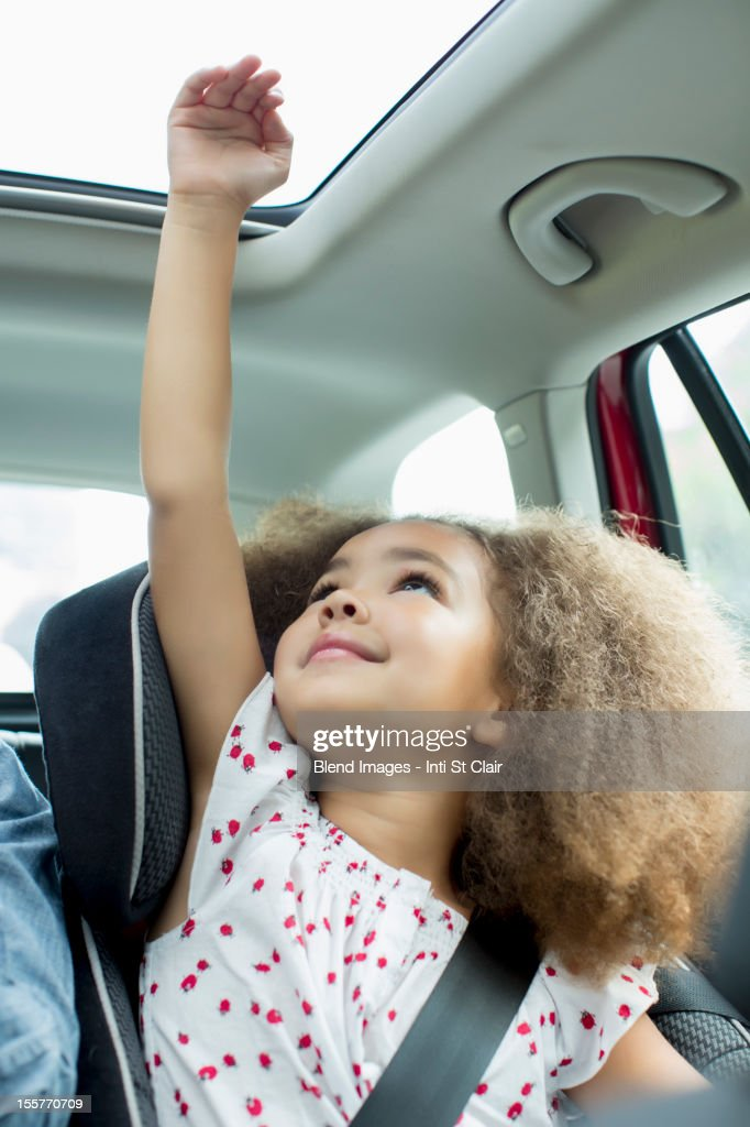 Mixed race girl sitting in car seat with arm out window : Stock Photo