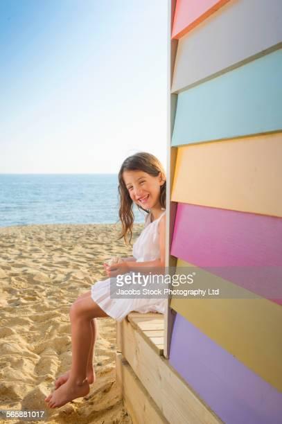 Mixed race girl sitting near colorful beach hut