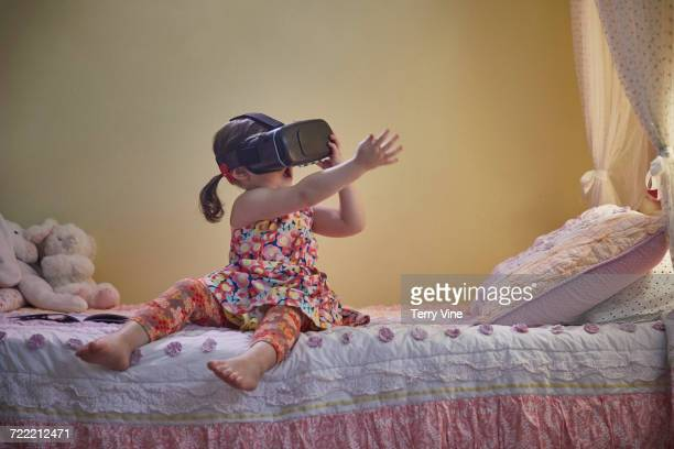 Mixed Race girl sitting on bed using virtual reality goggles