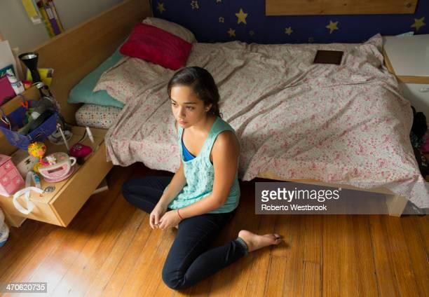 Mixed race girl sitting on bedroom floor