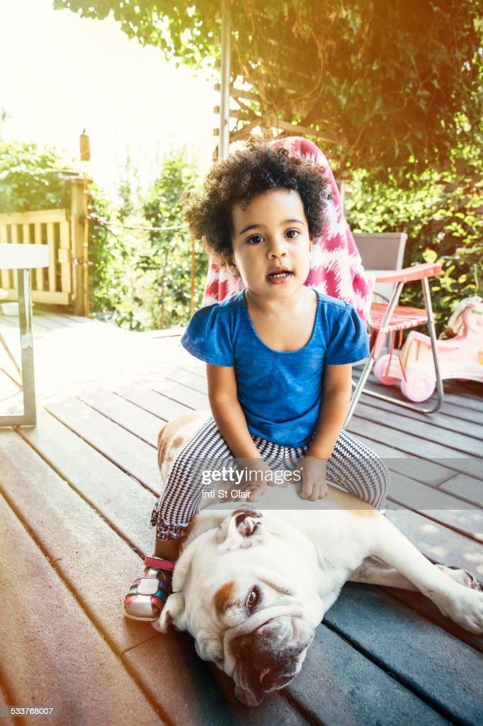 Mixed race girl sitting on dog on porch : Foto stock