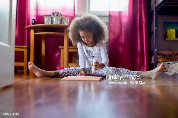 mixed race girl sitting on floor drawing - art and craft stock pictures, royalty-free photos & images