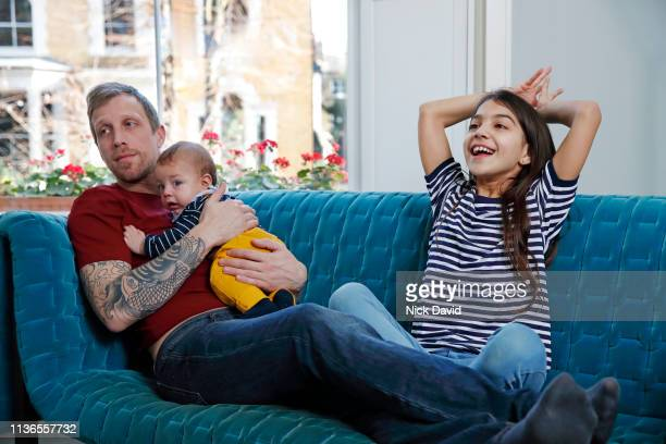Mixed race girl sitting on sofa with father and baby brother