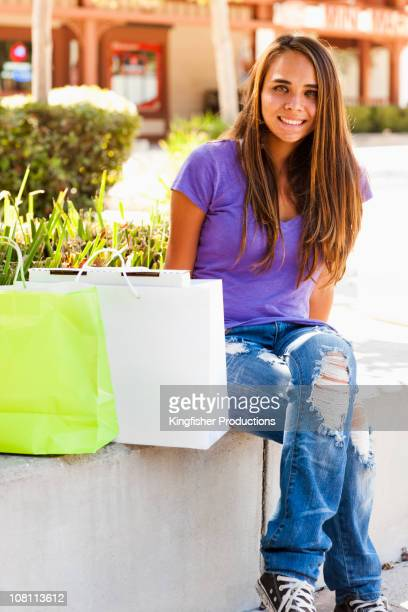 Mixed race girl sitting outdoors with shopping bags