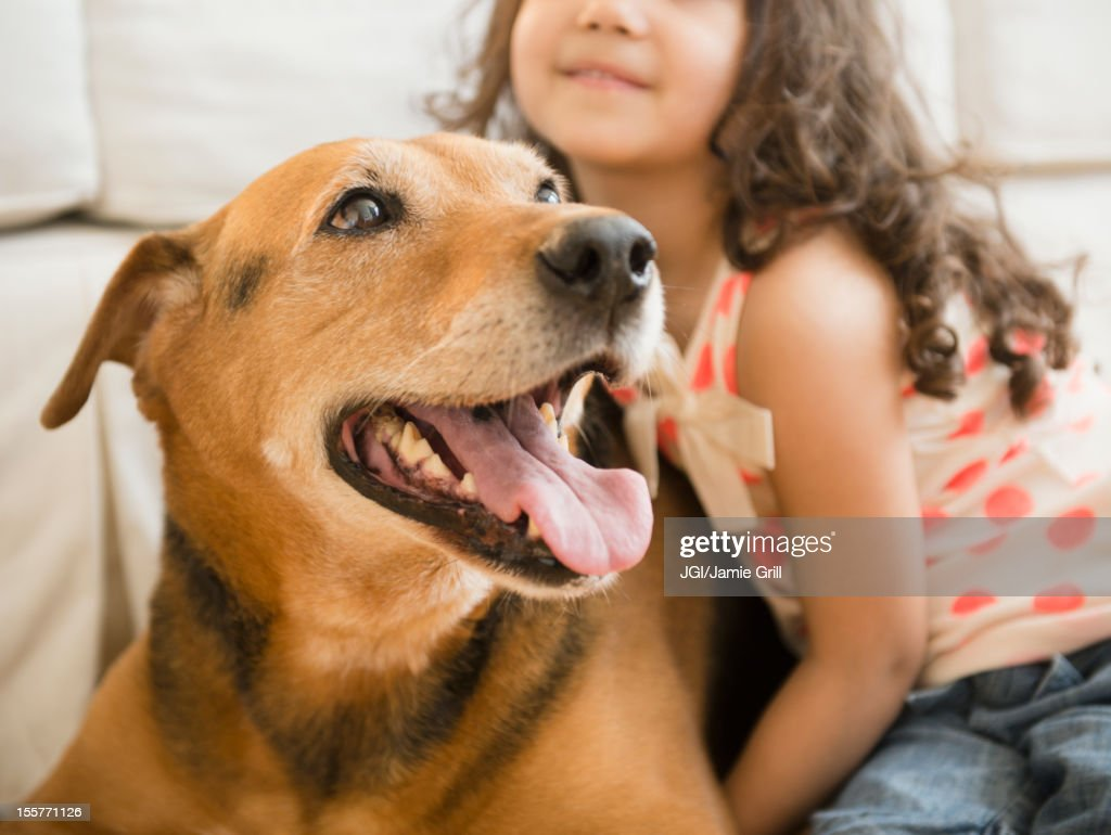 Mixed race girl sitting with dog : Stock Photo
