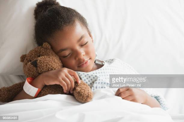 mixed race girl sleeping in hospital bed with teddy bear - girl in hospital bed sick stock photos and pictures