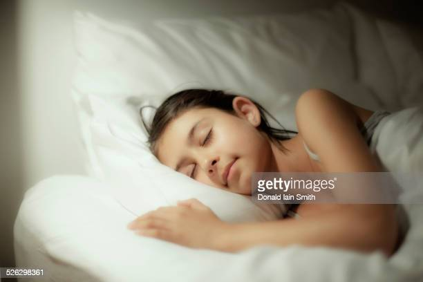 Mixed race girl sleeping on bed