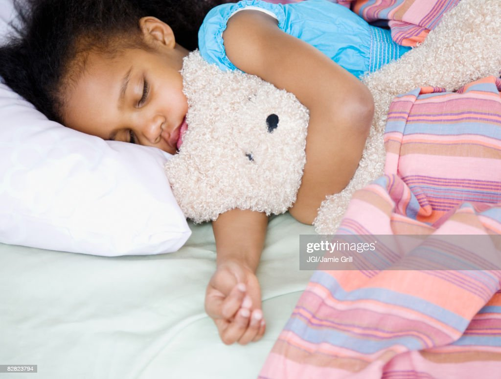 Mixed race girl sleeping with teddy bear : Stock Photo