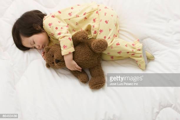 Mixed race girl sleeping with teddy bear