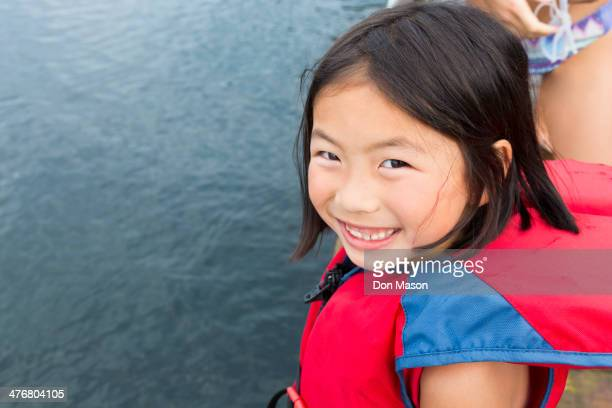 Mixed race girl smiling by lake