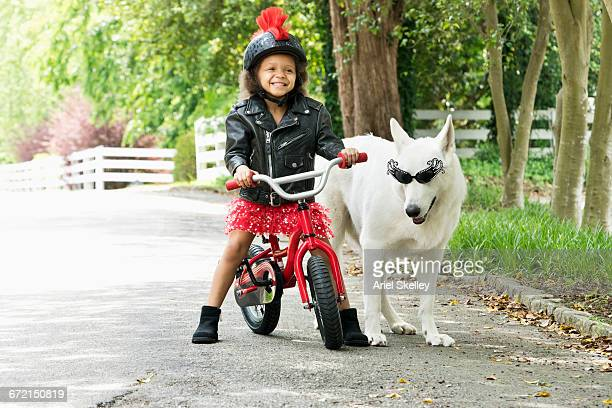 Mixed Race girl smiling in leather jacket on bicycle with dog