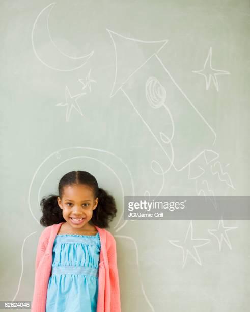 Mixed race girl standing by drawings on blackboard