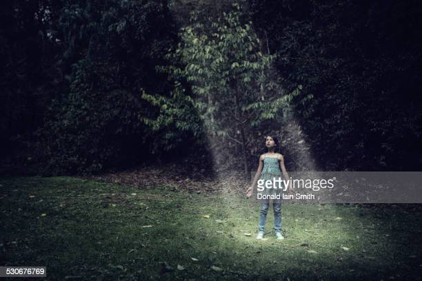 Mixed race girl standing in beam of light outdoors
