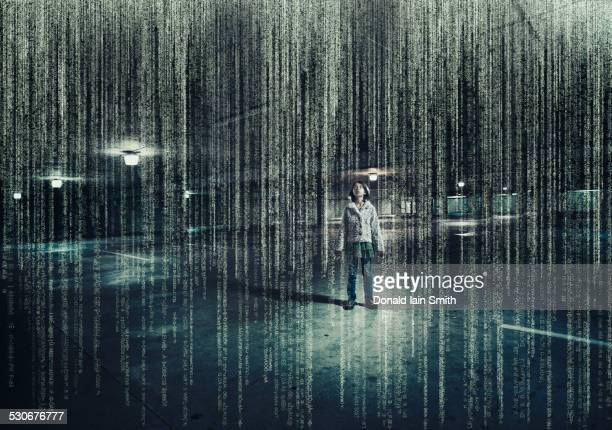 mixed race girl standing in parking lot under raining binary code - binary code stock pictures, royalty-free photos & images