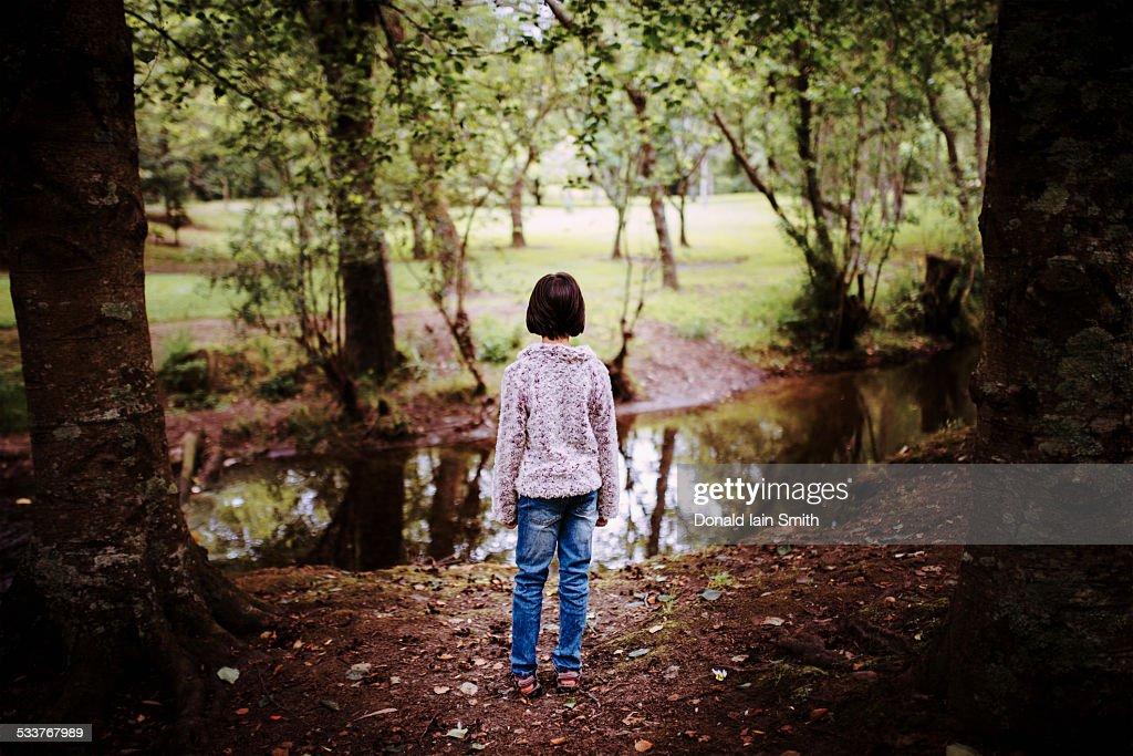 Mixed race girl standing near still creek : Foto stock