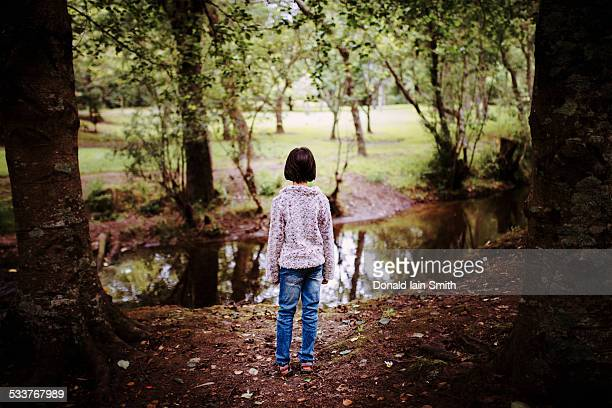 mixed race girl standing near still creek - black hair stock pictures, royalty-free photos & images