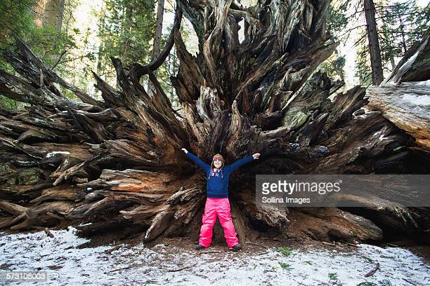 Mixed race girl standing under uprooted tree in forest