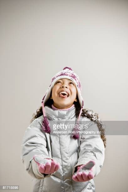 Mixed Race girl sticking out tongue in snow
